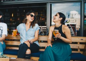 Two women sitting next to each other on a bench, holding glasses of beer and laughing.